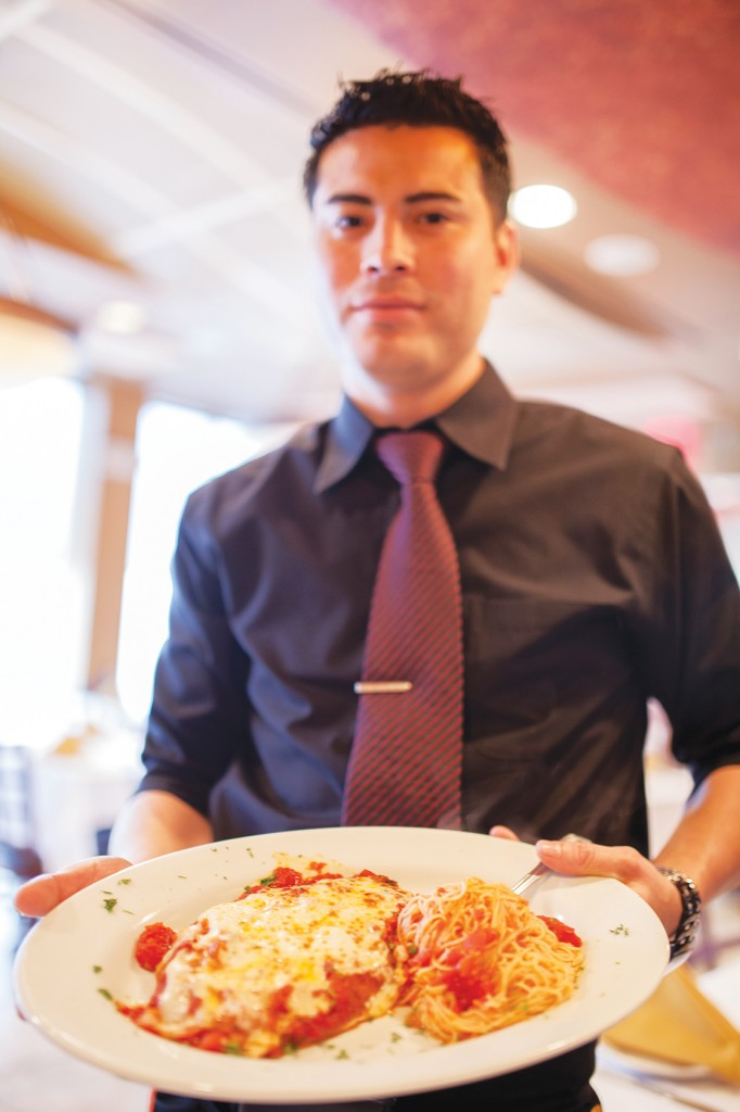 Douglas Garcia, a waiter of four years at Piccolo Trattoria in Pennington NJ, serving chicken parmesan.  Photo by Zac Santanello